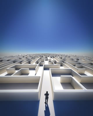 Business man standing facing a large maze